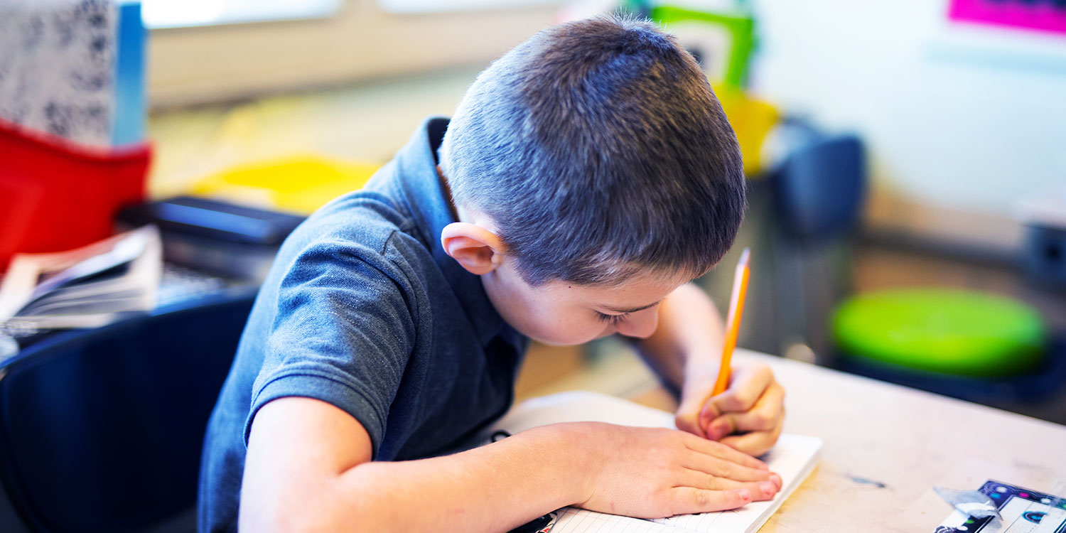 Student writing in a notebook at their desk in a classroom.