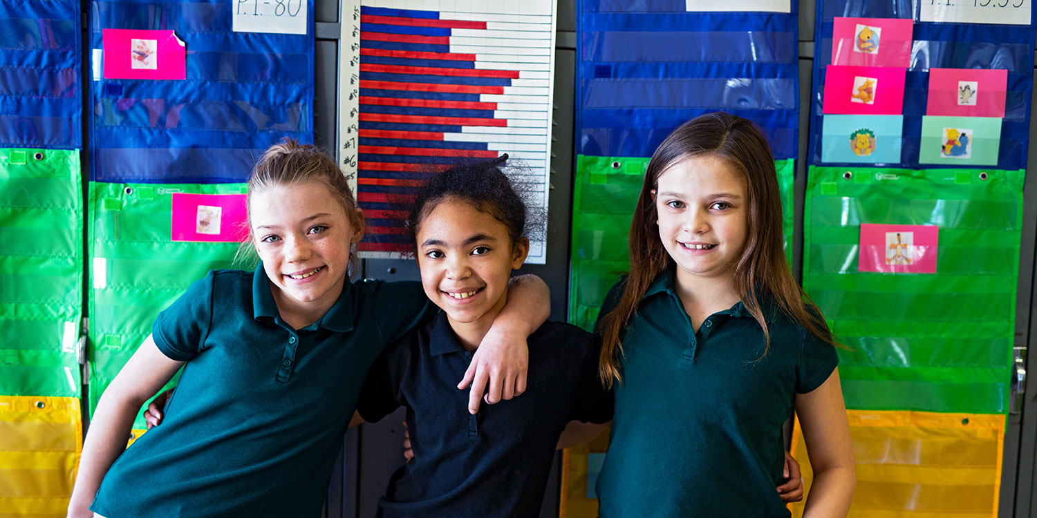 Smiling students standing together in a classroom.