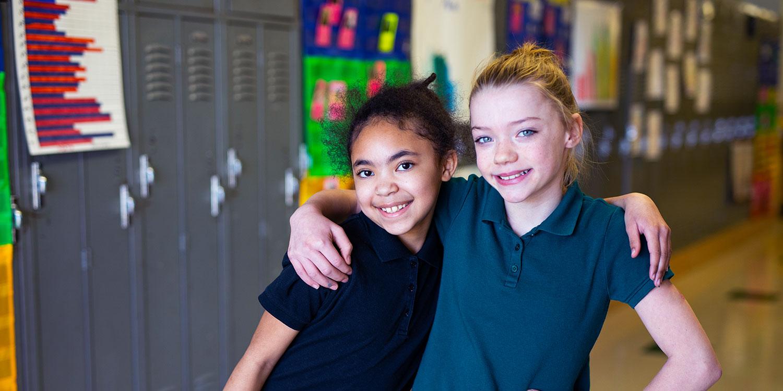 Smiling students in school hallway.